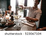 young man pouring wine from the ... | Shutterstock . vector #523067104
