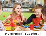 Stock photo group of pupils sitting at table in school cafeteria eating lunch 523108579