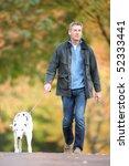 Stock photo man walking dog through autumn park listening to mp player 52333441