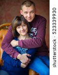 Small photo of Happy couple sit on a chair. Amicably embrace and smile. Strong family
