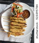 Small photo of Peanut sashay chicken skewers and green salad on a plate, Kathmandu, Nepal
