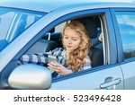Young woman using her smartphone while driving a car