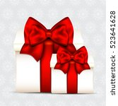 two gift boxes with red bow... | Shutterstock .eps vector #523641628