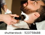 master cuts hair and beard of... | Shutterstock . vector #523758688
