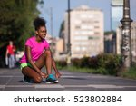 Small photo of African american woman runner tightening shoe lace - Fitness, people and healthy lifestyle