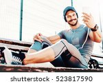 young muscular man sitting on a ... | Shutterstock . vector #523817590