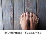 male feet on wooden background. | Shutterstock . vector #523837453