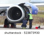 Stock photo technicians checking jet engine of civil airplane 523873930