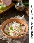 Small photo of Salad with sauerkraut, ham, apple and green peas. Snack on a festive table.