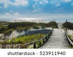 A Wooden Pathway Over The Sand...
