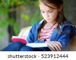 Cute Little Girl Reading A Boo...