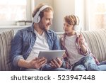 father and son in headphones... | Shutterstock . vector #523947448