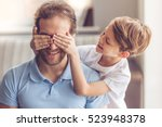 Small photo of Father and son are smiling while spending time together. Little boy is covering his dad eyes