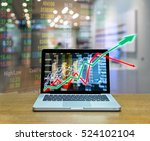 Small photo of Stock exchange market trading graph over the screen of computer laptop on wood table over the photo blurred of trading graph background, business marketing trade concept