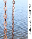 Small photo of Metal chain links above water.