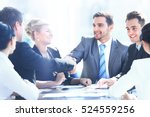 Small photo of Business colleagues sitting at a table during a meeting with two male executives shaking hands