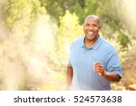 middle aged man jogging in park | Shutterstock . vector #524573638