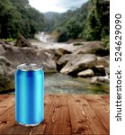 Stock photo blue can on wood table with blur waterfall background 524629090
