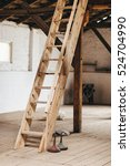 Small photo of Wooden attic ladder stairs in a rustic interior.