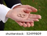 Bride and groom showing their wedding rings on their palms - stock photo