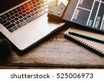 Stock photo office stuff with movie clapper laptop and pencil notepad on the wood table top view shot dark 525006973