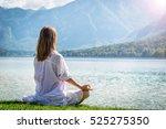 woman meditating at the lake | Shutterstock . vector #525275350