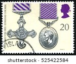Small photo of GREAT BRITAIN - CIRCA 1990: A used postage stamp from the UK, depicting an illustration of a Distinguished Flying Cross and Distinguished Flying Medal, circa 1990.