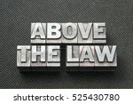 Small photo of above the law phrase made from metallic letterpress blocks on black perforated surface