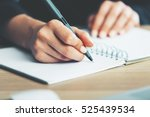 Small photo of Close up of woman's hands writing in spiral notepad placed on wooden desktop with various items
