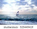 windsurfer surfing through wavy ... | Shutterstock . vector #525449419