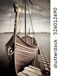 Small photo of A moored Viking boat with a dragonhead on a bow and an accommodation ladder. Low color saturation for a faded retro or vintage effect