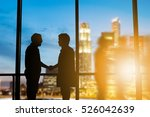 Small photo of Silhouette businessmen shake hands finishing a deal between businesses Success of the joint venture business growth progress and potential concept over blurred employees the city night and flare light