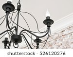 Small photo of Bending metal parts black chandelier with lamps in the form of candles in classic style. On the background of white washed brick wall. Rustic, shabby chic, Provence, classic.