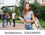 Stock photo happy cute young woman student with backpack holding books and walking outdoors 526144693
