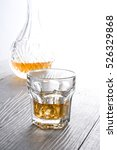 Small photo of Glass of scotch whiskey on wooden table. Alcoholic beverage