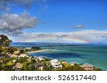 Tahunanui Beach in Nelson, New Zealand. Rainbow visible in the distance.