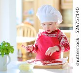 Small photo of Smiling little child, wearing red chef apron and white hat, preparing pizza for family party topping it with tomato sauce, vegetables and cheese, sitting at dining table at bright sunny room at home