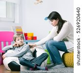 Small photo of Little boy afraid of hand's touch of young worried psychologist trying to help