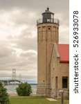 Small photo of MACKINAW CITY, MI/USA - JULY 15, 2016: Old Mackinac Point Lighthouse and Mackinac Bridge on a blustery day, between Lake Michigan and Lake Huron, in Colonial Michilimackinac Park, Michigan.