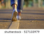 Stock photo woman jeans and sneaker shoes walking on the road sunset light 527133979