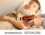 woman pouring syrup for sick boy | Shutterstock . vector #527241250