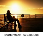 Tourist Sit On Wharf Bench And...