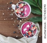 Small photo of acai berry smoothie bowls on wood background. top view
