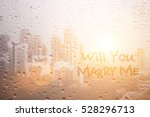 Small photo of write will you marry me on raining window in first light morning time