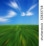 Abstract motion with a green grass landscape and a blue sky - stock photo