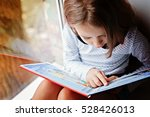 Toddler girl with book near the ...