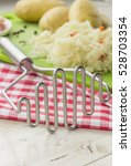 Small photo of Potato masher and ingredients for typical dutch dish zuurkool with sauerkraut and potatoes