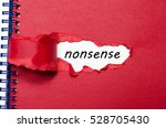 Small photo of The word nonsense appearing behind torn paper