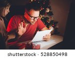 Small photo of Busy father reading letter late at night in a home office and ignore his daughter