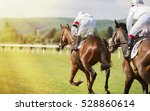 Stock photo two horses and jockeys competing in the race the sunlit path and two jockeys on racing horses 528860614